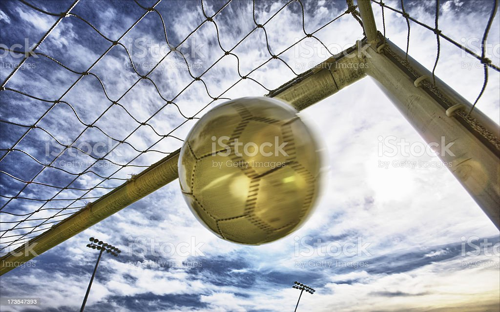 Gold soccer bold shot in to the top corner royalty-free stock photo