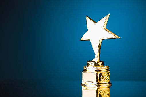 istock gold star trophy against blue background 498910514