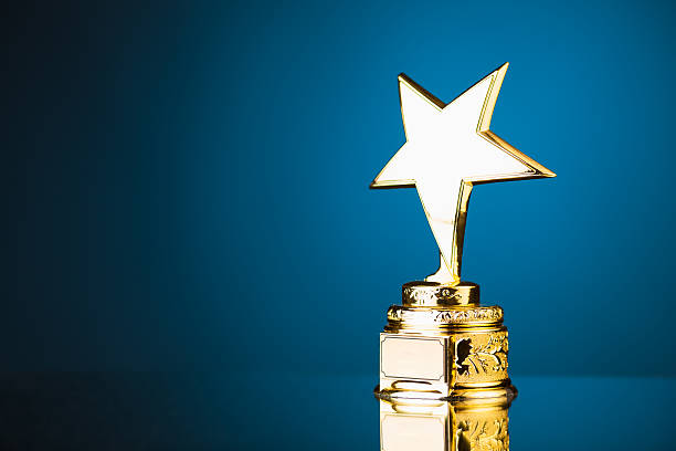 gold star trophy against blue background - trophy award stock photos and pictures