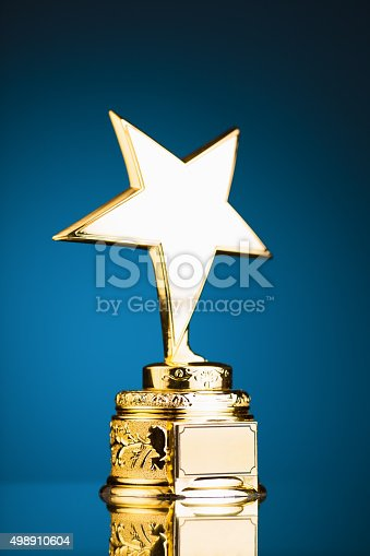 498910514istockphoto gold star trophy against blue background 498910604