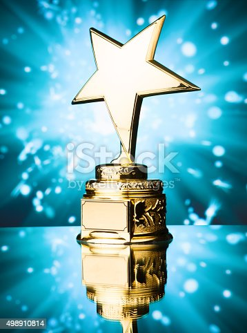 498910514istockphoto gold star trophy against blue background 498910814