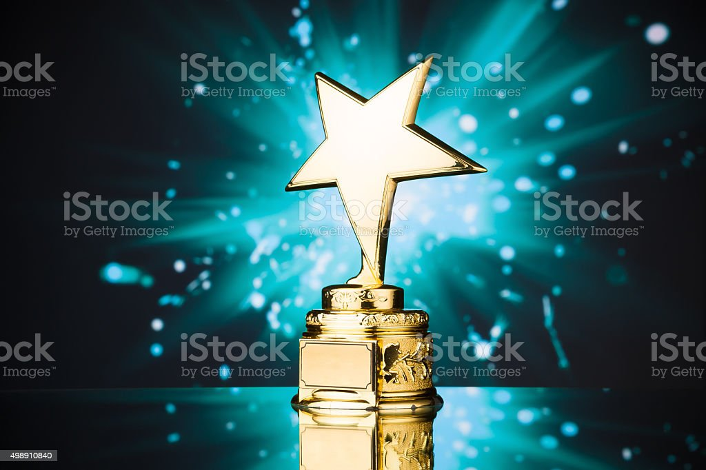 gold star trophy against blue background stok fotoğrafı