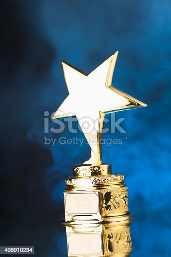 498910514istockphoto gold star trophy against blue smoke background 498910234