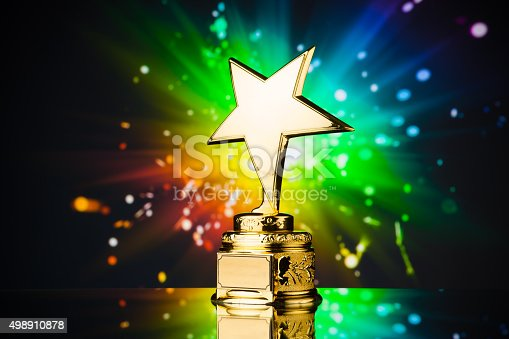 498910514istockphoto gold star trophy against rainbow background 498910878