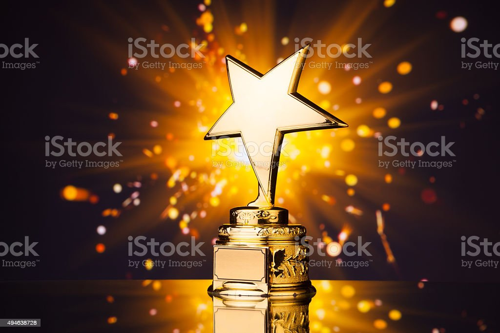 gold star trophy against shiny sparks background stock photo