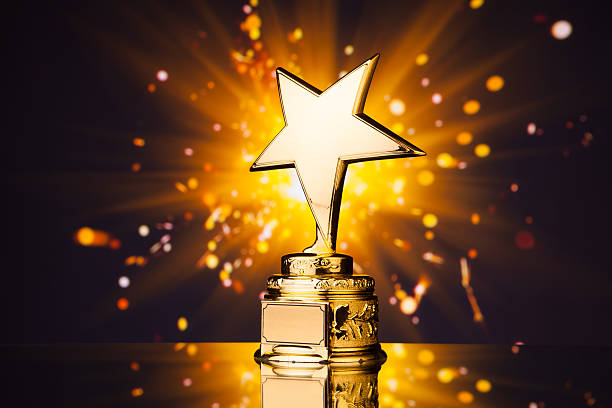 gold star trophy against shiny sparks background - trophy award stock photos and pictures