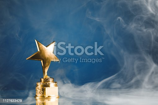 498910514istockphoto gold star trophy in smoke, blue background 1127633429