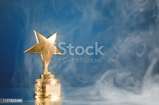 498910514istockphoto gold star trophy in smoke, blue background 1127633469
