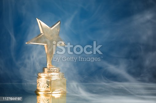 498910514istockphoto gold star trophy in smoke, blue background 1127644197