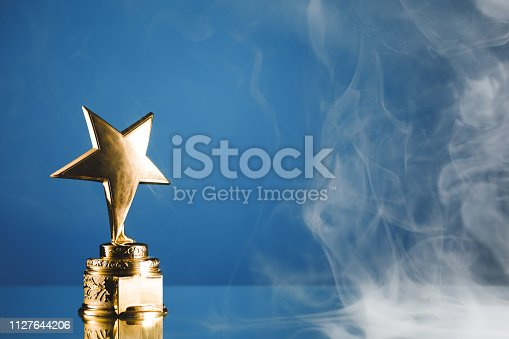 498910514istockphoto gold star trophy in smoke, blue background 1127644206
