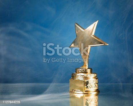 498910514istockphoto gold star trophy in smoke, blue background 1127644225