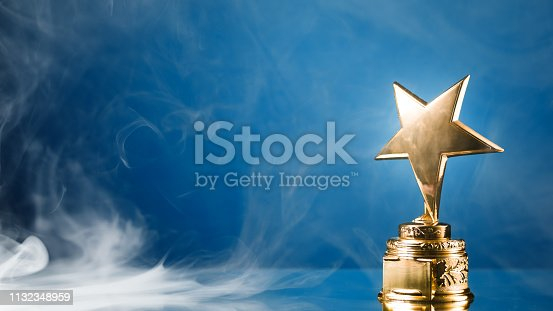 498910514istockphoto gold star trophy in smoke, blue background 1132348959