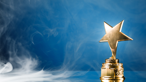 istock gold star trophy in smoke, blue background 1132348959
