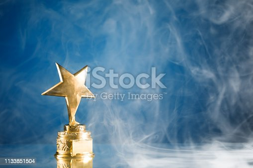 498910514istockphoto gold star trophy in smoke, blue background 1133851504