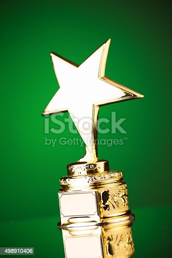 498910514istockphoto gold star trophy on green background 498910406