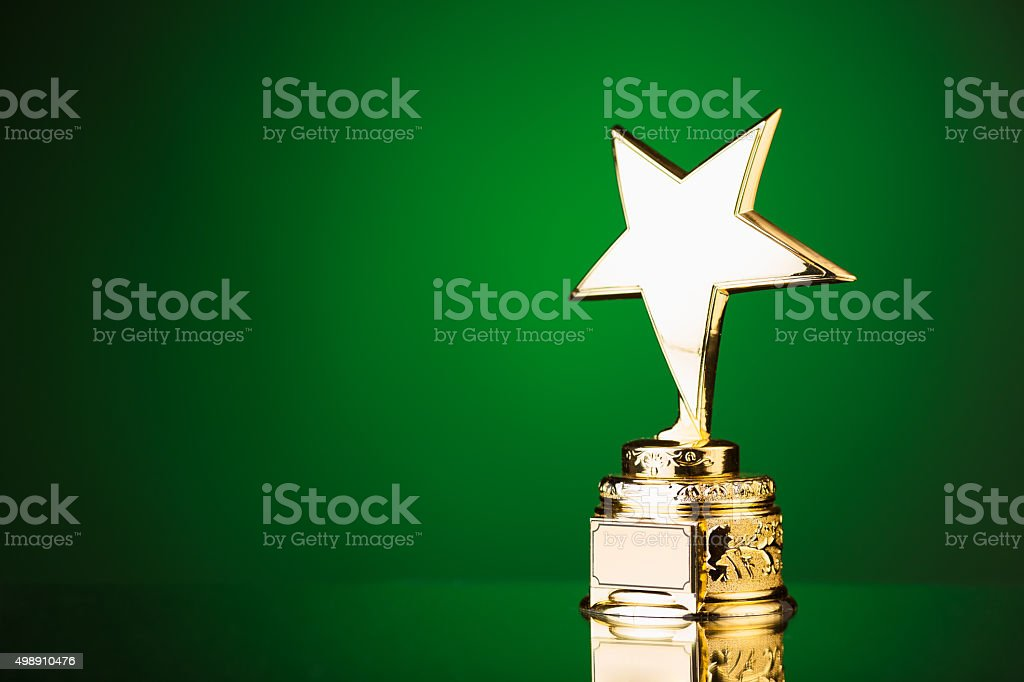 gold star trophy on green background stock photo