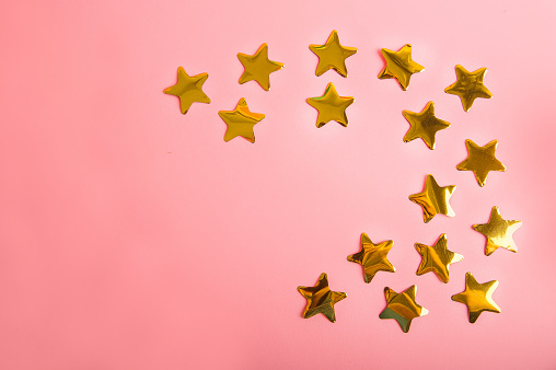 Gold stars confetti on a pink background. Golden  confetti close-up and copy space.