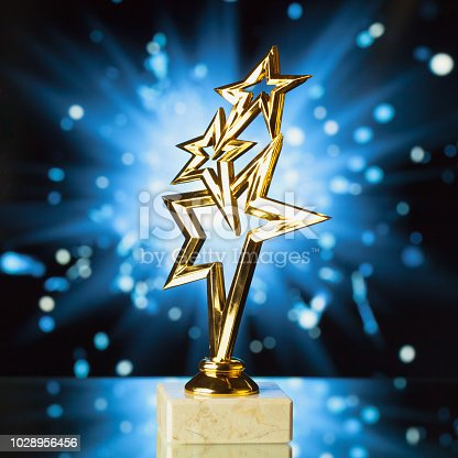 498910514istockphoto gold stars trophy against shiny sparks background 1028956456