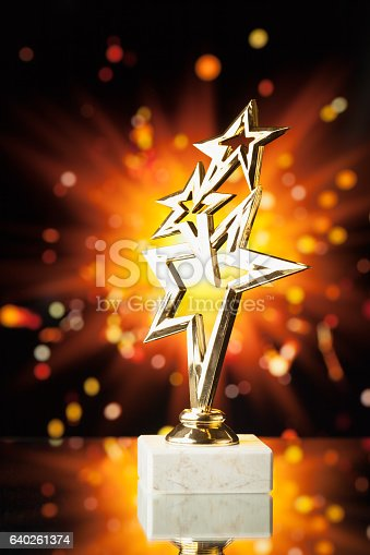 istock gold stars trophy against shiny sparks background 640261374