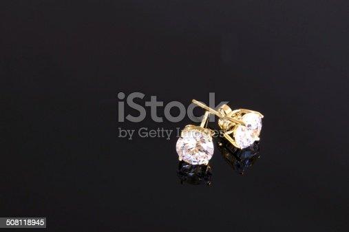 Gold stud diamond earrings on black background.