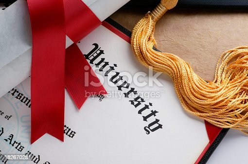 A red ribbon wrapped around a rolled up diploma sits on top of a another college diploma.  A gold tassel from a graduation cap is also draped across the diploma.