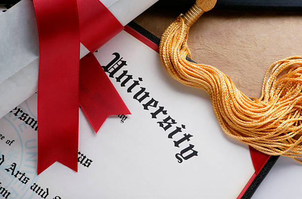 Gold tassel and rolled diploma with red ribbon stock photo