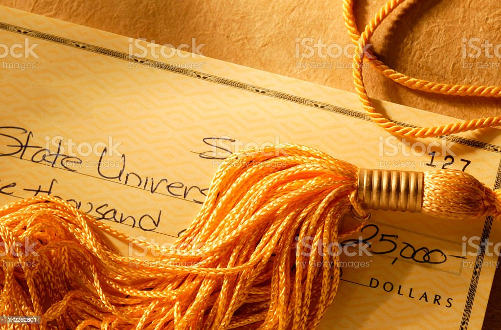 Gold tassel on a check written for college tuition royalty-free stock photo