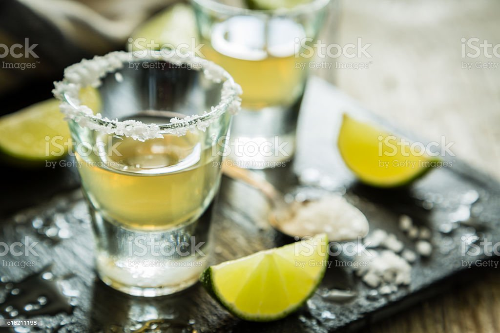 Gold tequila shots on rustic wood background stock photo