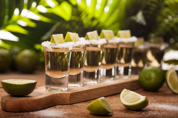 Gold tequila shots with lime fruits stock photo