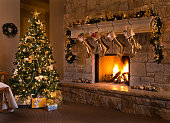 A beautiful contemporary gold-themed Christmas Eve fireplace, tree, stockings, and living room. Stockings hanging from mantel by fireplace, and gifts under tree.