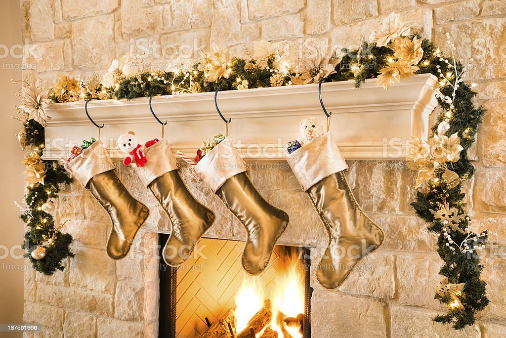gold theme christmas stockings hanging from mantel by fireplace royalty free stock photo