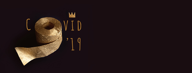 Gold toilet paper with a crown on a black background. A concept on the topic of coronavirus and pandemic.