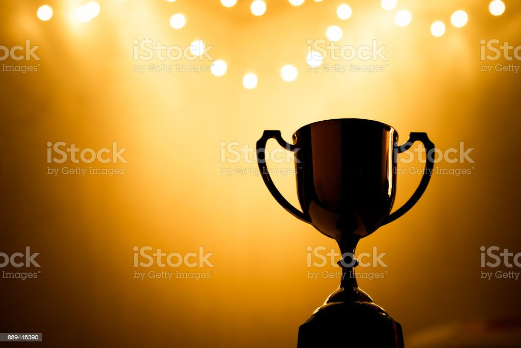 Gold Trophy competition in the dark on the abstract blurred light background with copy space, Spectacular success Concept stock photo
