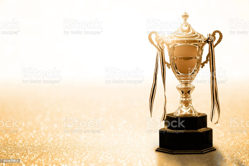 Gold Trophy competition on the abstract glitter background with copy space stock photo