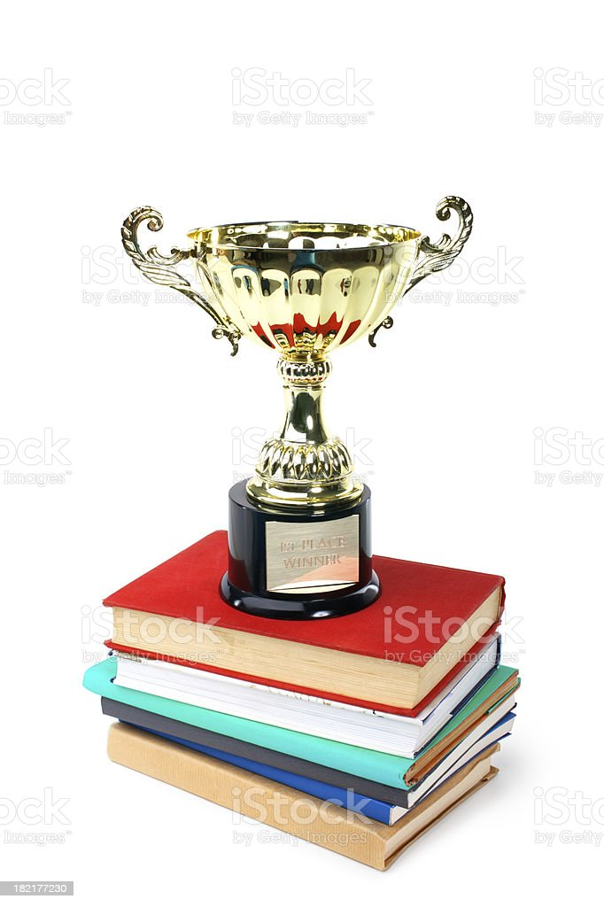 Gold trophy placed on a stack of books royalty-free stock photo