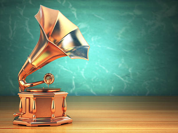 Gold vintage gramophone on green background. stock photo