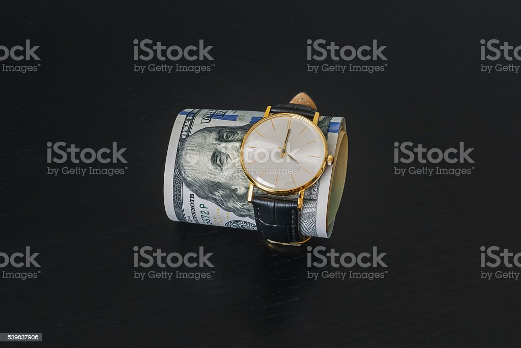 gold watch on dollar money banknotes stock photo