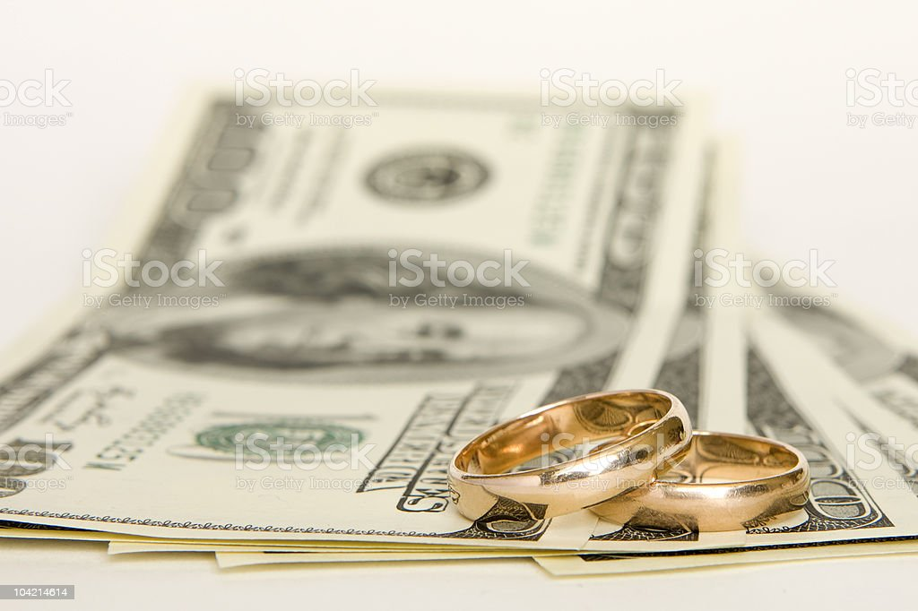 2 gold wedding bands on top of 100-dollar bills stock photo