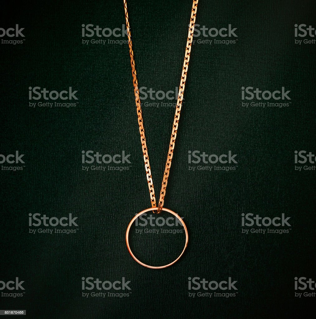 Gold Wedding Ring Hanging On Gold Chain On Black Background Stock