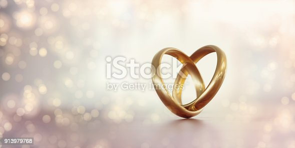 Gold wedding rings forming a heart shape over pale background. Great use for wedding, love and romance concepts. Isolated on white background. Panoramic composition.