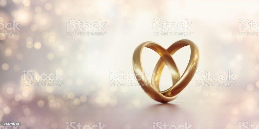 Bagues de mariage or formant une forme de coeur sur fond pâle - Photo