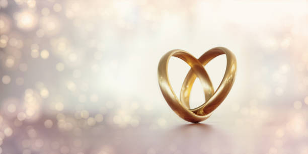 Gold Wedding Rings Forming A Heart Shape Over Pale Background Gold wedding rings forming a heart shape over pale background. Great use for wedding, love and romance concepts. Isolated on white background. Panoramic composition. honeymoon stock pictures, royalty-free photos & images