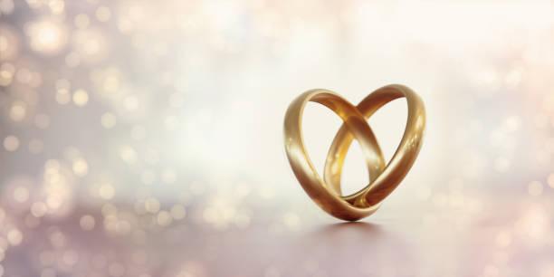 gold trauringe bilden eine herzform über blassen hintergrund - heiratsantragsring stock-fotos und bilder
