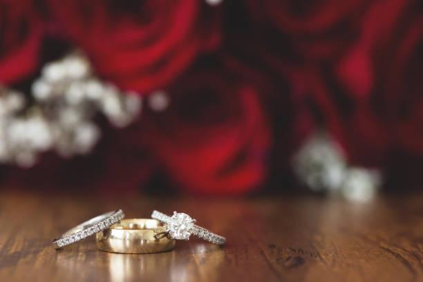 gold trauringe mit roten rosen - tischdeko goldene hochzeit stock-fotos und bilder