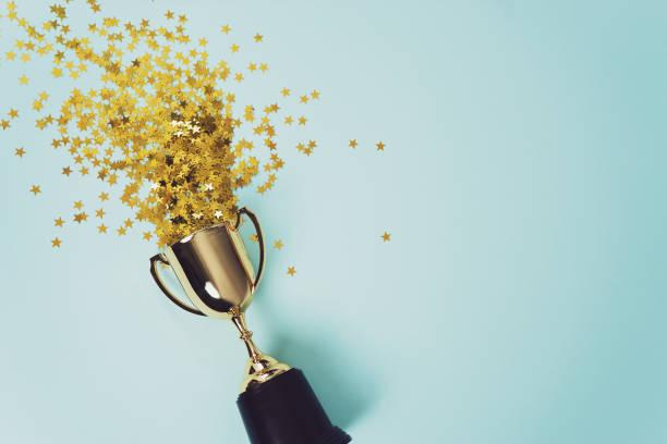 金牌優勝者杯子在藍色背景 - 成功 個照片及圖片檔