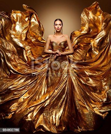 istock Gold Woman Flying Dress, Fashion Model Waving Golden Gown, Fluttering Wings Fabric, Art Beauty Portrait 934802786