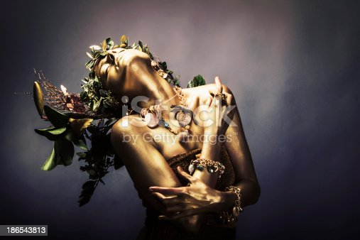 Attractive female painted gold,wearing jewelry and branches on her head.Studio creative shot.