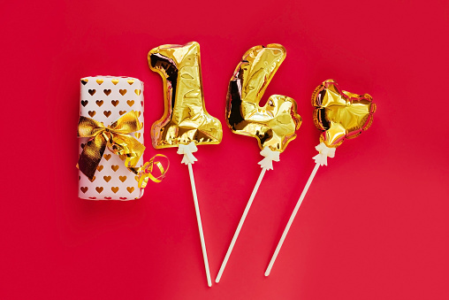 Golden 14 balloons, gift, souvenir heart isolated on red background. Helium balloons, gold foil numbers. Numbers for Valentine's day. Party decoration, celebration, carnival.