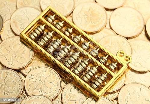istock Golden Abacus with Chinese rmb gold coins as background 682846024
