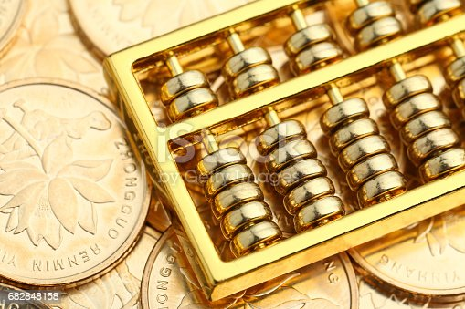 istock Golden Abacus with Chinese rmb gold coins as background 682848158